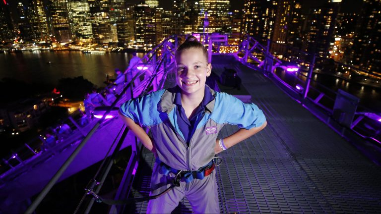 Charlotte Whitlock posing on the Story Bridge as part of Epilepsy Day, Brisbane 26th of March 2018.  The bridge is lit up in purple lights for Epilepsy Queensland for Purple Day.  (AAP Image/Josh Woning)